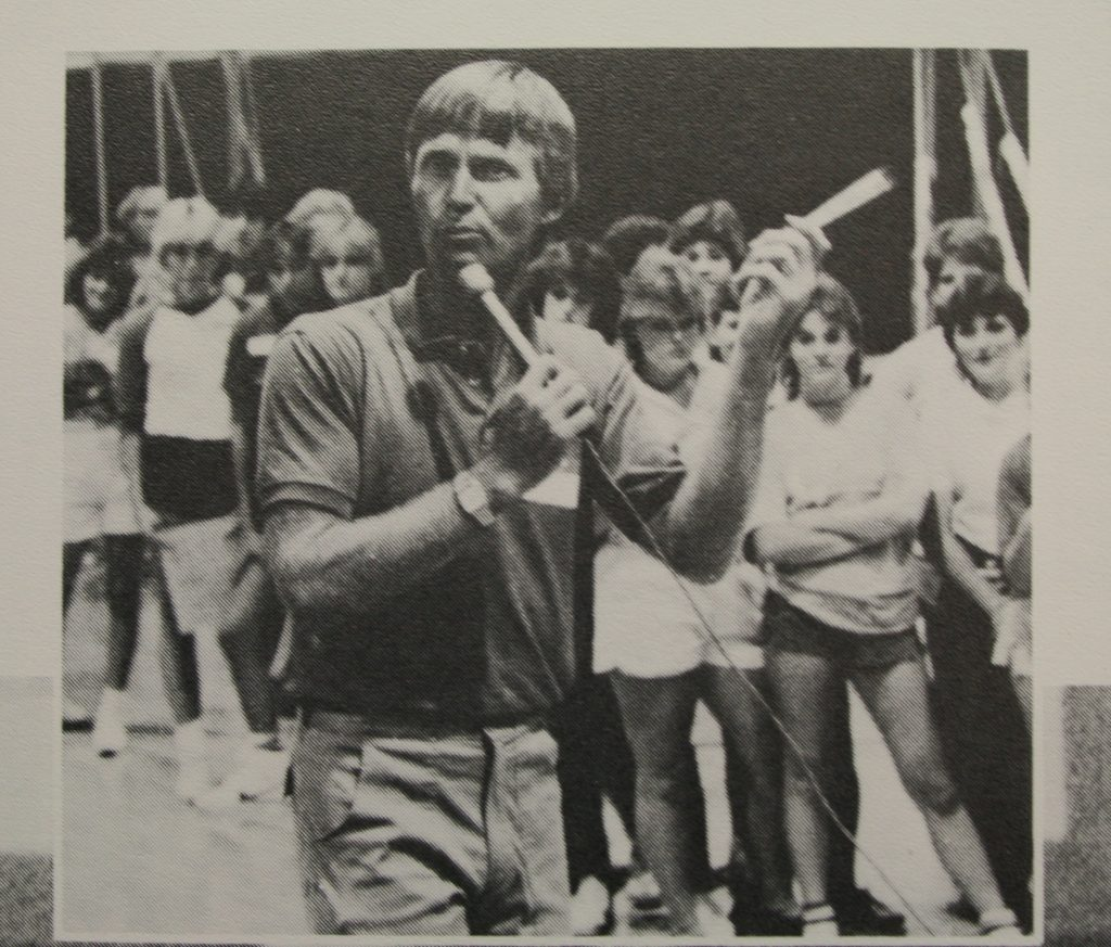 Photo of high school principal Ken Steine leading a student cheer session in the mid 80s..